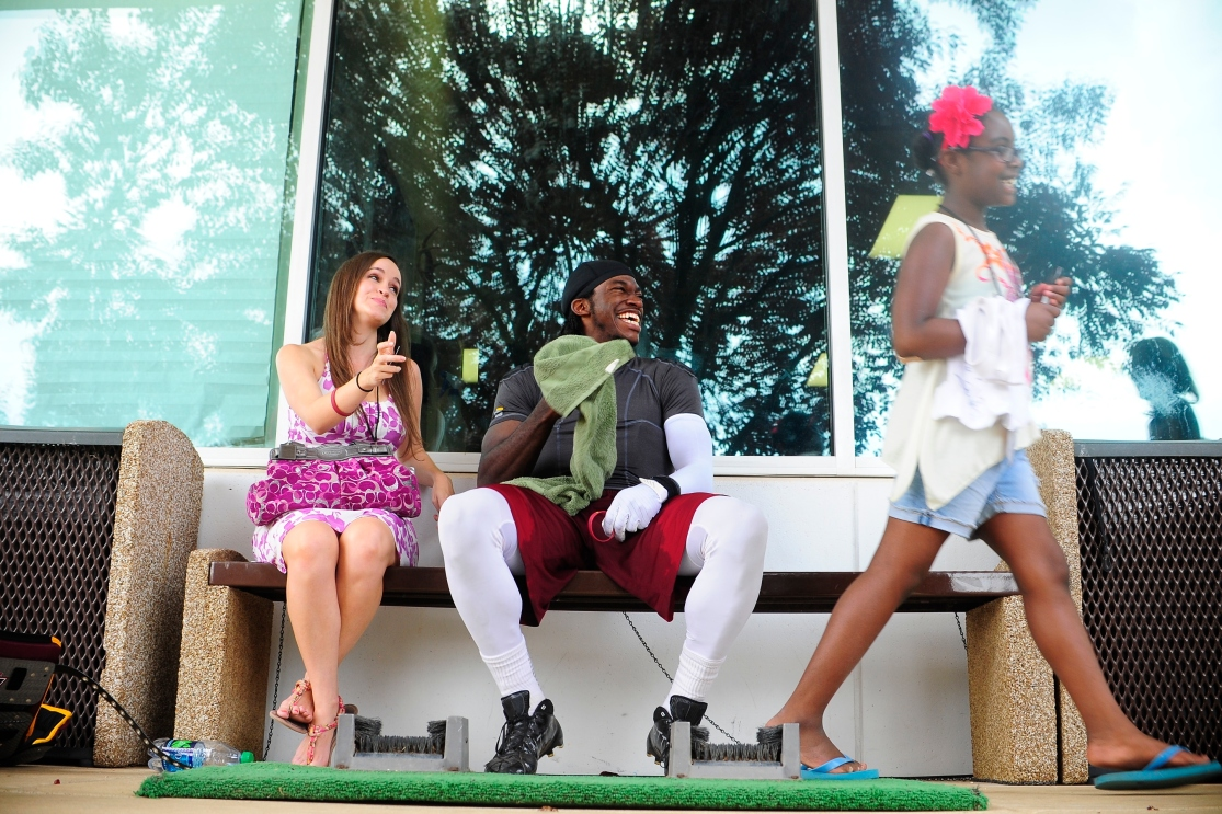 Robert Griffin III has a laugh on the bench with his fiance Rebecca Liddicoat after signing an autograph for a young fan following Redskins' training camp at Redskins Park, Ashburn, Va., Monday, July 30, 2012.